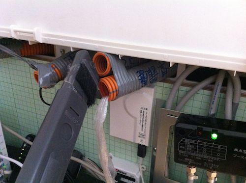 掃除機を空配管に押し当てる
