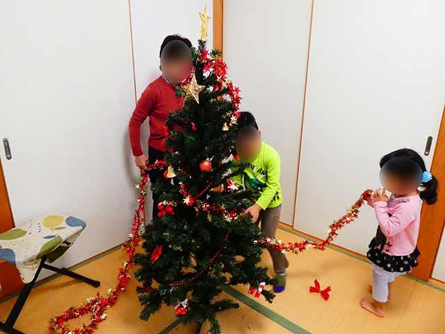 クリスマスツリーに飾りを巻きつける
